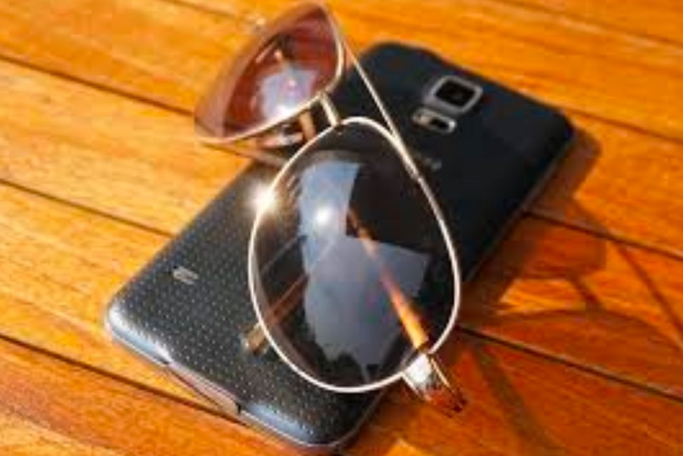 a pair of sunglasses on top of a cell phone lying on an outdoor deck.